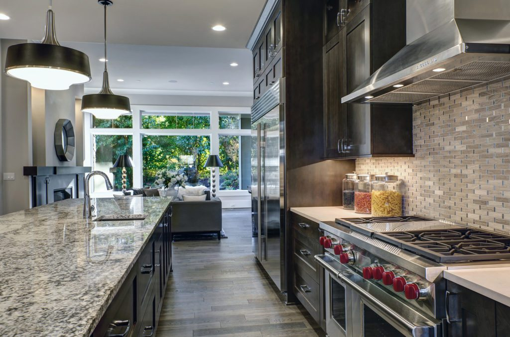 Modern kitchen with brown kitchen cabinets, oversized kitchen island with bar stools, granite countertops, huge refrigerator and beige backsplash